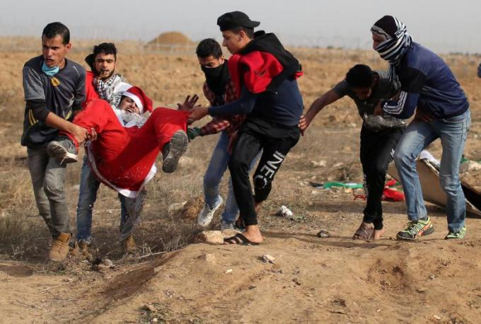 Wounded Palestinian demonstrator dressed as Santa Claus is evacuated during clashes with Israeli troops at a protest near the border with Israel in the southern Gaza Strip